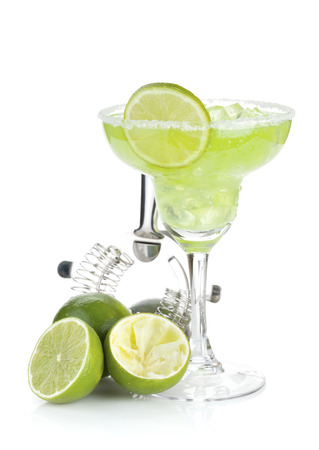margaritas: Classic margarita cocktail with salty rim, limes and drink utensils. Isolated on white  Stock Photo