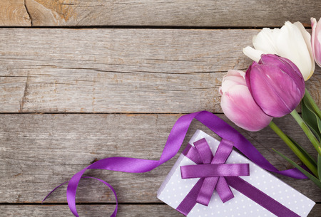 flower box: Fresh tulips with gift box over wooden table with copy space