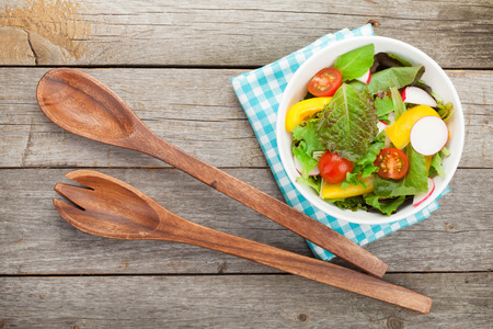 kitchen table top: Fresh healthy salad on wooden table and kitchen utensil.