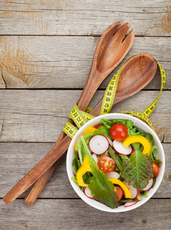 Fresh healthy salad on wooden table and kitchen utensil.