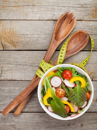 Verse gezonde salade op houten tafel en keuken gebruiksvoorwerp. Stockfoto