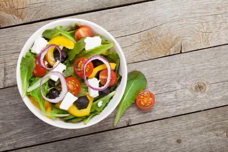 Ensalada sana fresca en mesa de madera.