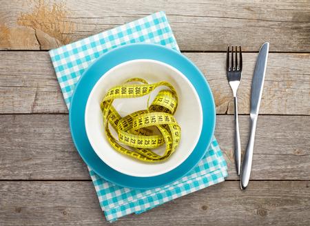 cintas metricas: Placa con la cinta métrica, cuchillo y tenedor. Alimento de la dieta en la mesa de madera