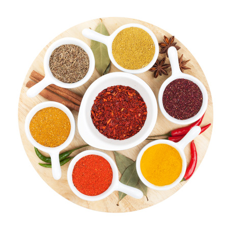 various: Various spices selection on cutting board. Isolated on white background