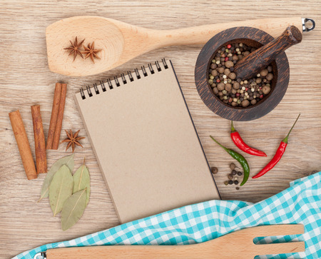 Various spices selection and notepad for copy space on wooden table photo