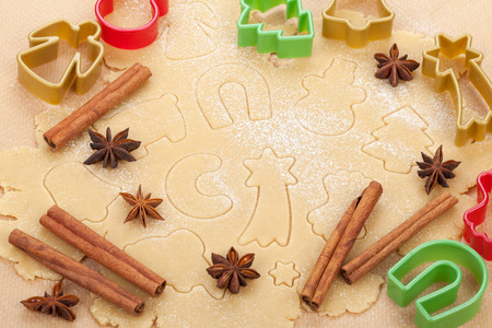 Gingerbread dough for christmas cookies with colorful cookie cutters and spices photo