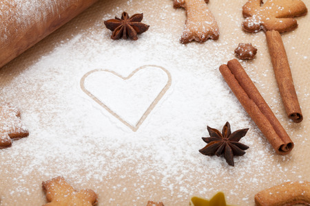 Rolling pin with flour and gingerbread cookies on cooking paper photo