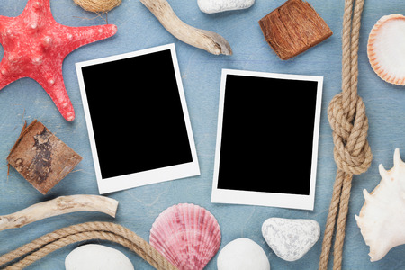 Travel photo frames on blue wooden texture with seashells and rope around photo
