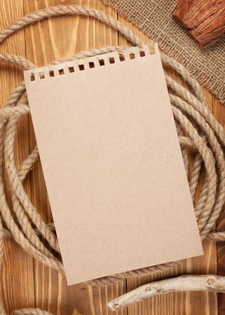 Paper for copy space and rope on wooden textured background photo