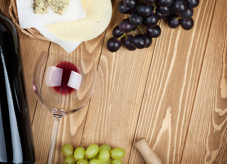 Red wine, cheese and grape on wooden table background with copy space photo