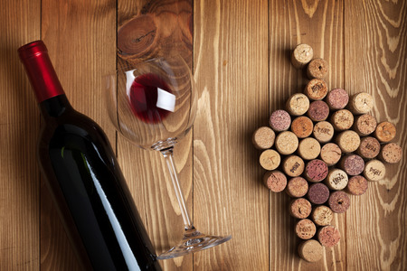 Red wine bottle, glass and grape shaped corks on wooden table background Stock Photo
