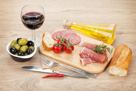 jamon y queso: Vino tinto con queso, aceitunas, tomates, jamón, pan y especias. Sobre fondo mesa de madera Foto de archivo