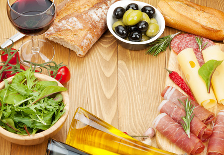 Red wine with cheese, prosciutto, bread, vegetables and spices on wooden table with copy space photo
