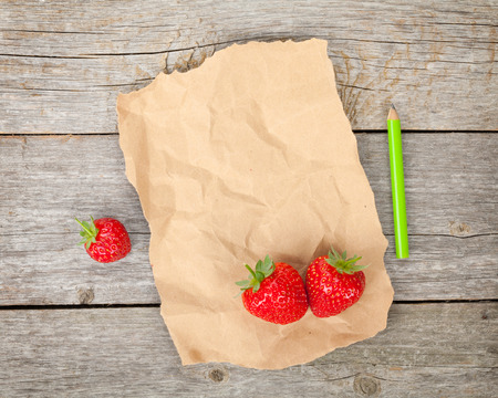 Blank paper with copy space and ripe strawberries over wooden table backgroun photo