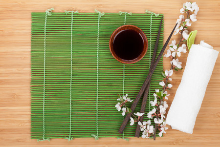 Chopsticks and sakura branch over bamboo mat with copy space photo