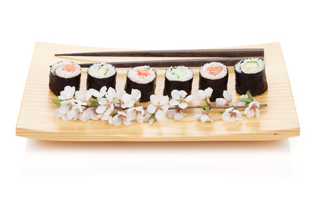 Sushi maki set with salmon and cucumber and sakura branch. Isolated on white background photo