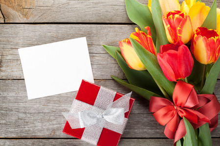 Fresh colorful tulips with gift box and greeting card over wooden background photo