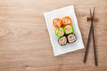 maki sushi: Sushi maki and chopsticks on wooden table. View from above with copy space