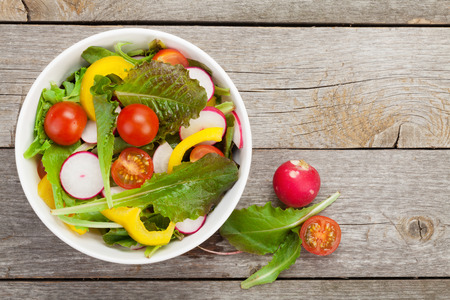 healty: Fresh healty salad on wooden table. View from above with copy space