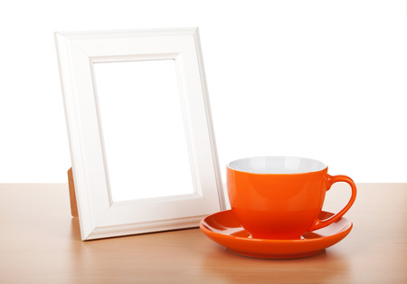 Photo frame and coffee cup on wooden table  Isolated on white background photo