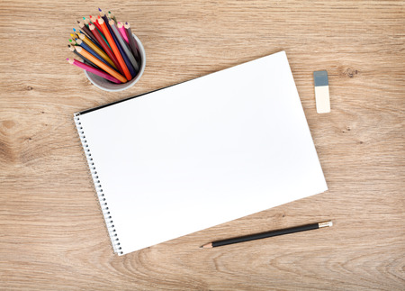 red pen: Blank paper and colorful pencils on the wooden table  View from above