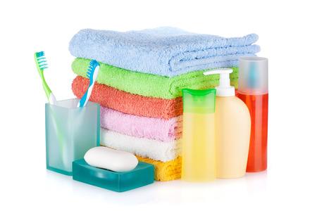 aseo personal: Dos cepillos de dientes de colores, botellas de cosméticos, jabón y toallas aislados sobre fondo blanco