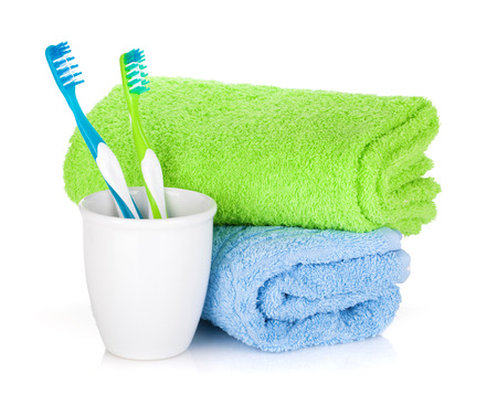 Two colorful toothbrushes and towels  Isolated on white background photo