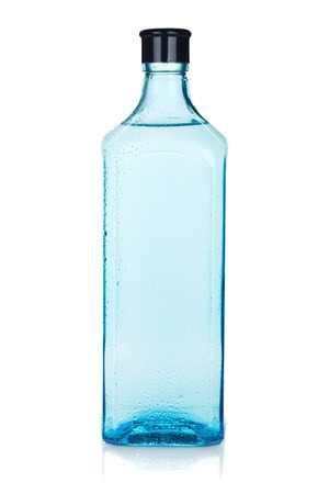 Glass gin bottle with water drops. Isolated on white background Banco de Imagens