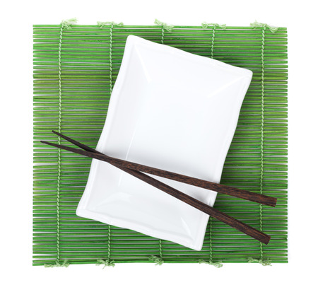 Chopsticks and plate over bamboo mat. Isolated on white background photo