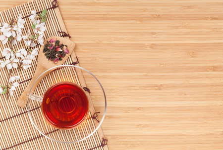 Japanese green tea and sakura branch over mat and bamboo table with copy space photo