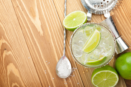 margarita drink: Classic margarita cocktail with salty rim on wooden table with limes and drink utensils Stock Photo