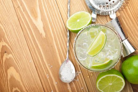 margarita cóctel: Coctel clásico del margarita con borde salado en mesa de madera con limones y utensilios de bebida