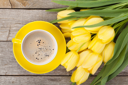 Fresh yellow tulips bouquet and coffee cup over wooden table 版權商用圖片