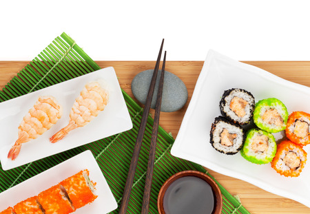 Sushi maki and shrimp sushi on bamboo board. Isolated on white background with copy space photo