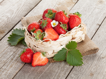 Fresh strawberry in basket on wooden table background photo