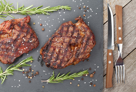 Beef steaks with rosemary and spices on wooden table photo