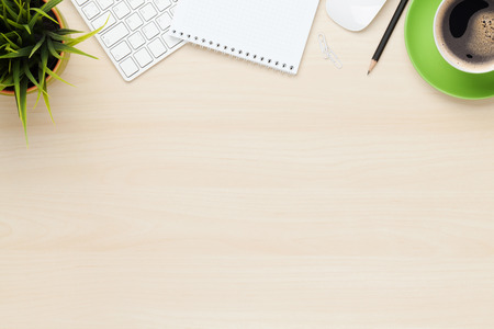 Kantoor tafel met kladblok, computer en een koffiekopje. Uitzicht van bovenaf met een kopie ruimte