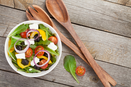 greek salad: Fresh healty salad on wooden table and kitchen utensil. View from above Stock Photo