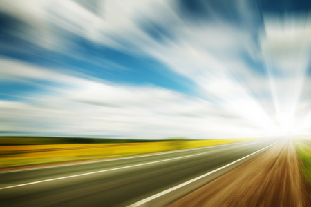 Road through the yellow sunflower field with clouds on blue sky motion blur