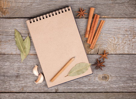 old notebook: Blank notepad for copy space and herbs on wooden table