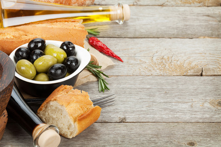 Italian food appetizer of olives, bread and spices on wooden table background with copy space photo