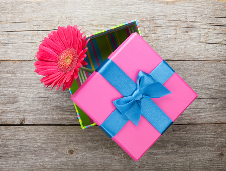 wood box: Purple gerbera flower in gift box on wooden table Stock Photo