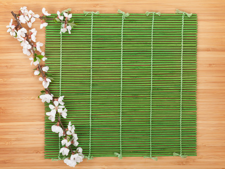Sakura branch over bamboo mat with copy space photo