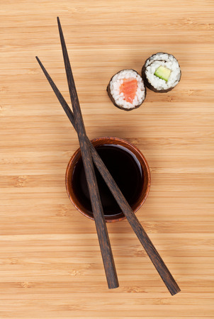 Maki sushi, chopsticks and soy sauce on bamboo wooden table  photo