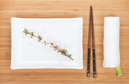Empty plate, chopsticks and sakura branch over bamboo table photo
