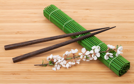 Chopsticks and sakura branch over bamboo mat photo