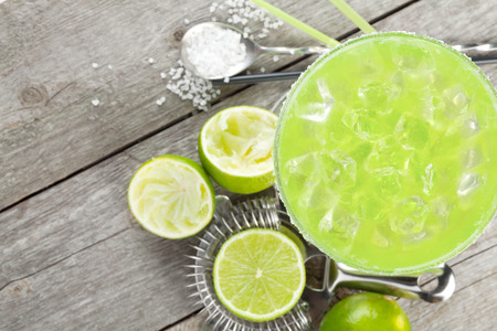 margaritas: Classic margarita cocktail with salty rim on wooden table with limes and drink utensils Stock Photo
