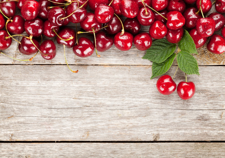 Ripe cherries on wooden table. View from above with copy space photo