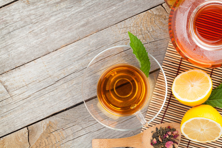 yellow tea pot: Green tea with lemon and mint on wooden table. View from above
