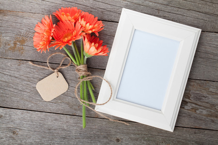 Bunch of gerbera flowers and photo frame on wooden table